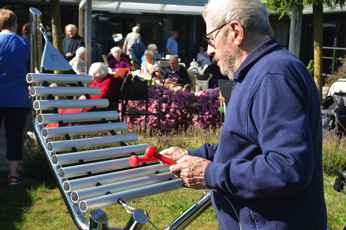 Older man playing an outdoor xylophone in care ome garden