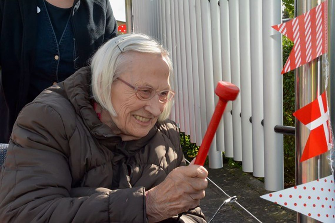 older lady in a wheelchair playing an outdoor musical instrument