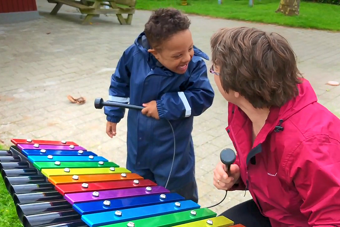 little boy with special needs playing a rainbow coloured outdoor xylophone with his teacher