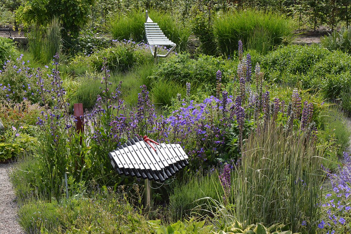 outdoor xylophone nestled among plants and flowers in a sensory garden